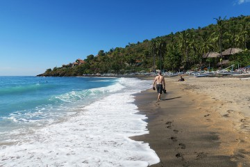 Enjoying a leisurely stroll along a volcanic beach in Amed.